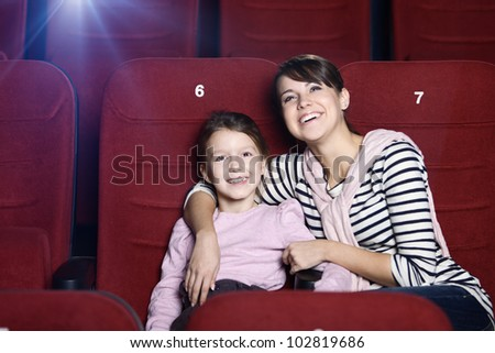 Toddler girl with mother in the movie theatre - stock photo