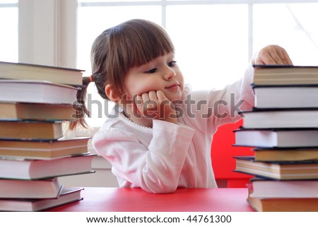 Toddler girl with pile of books on the table
