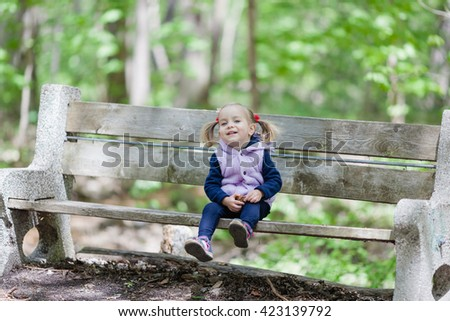 Toddler girl 2 years old sitting on the bench in green park. Spring time. Selective focus, natural light. Child looking straight to the camera. - stock photo