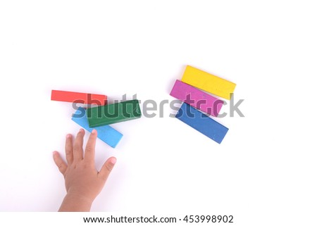 Toddler hand playing with colour blocks
