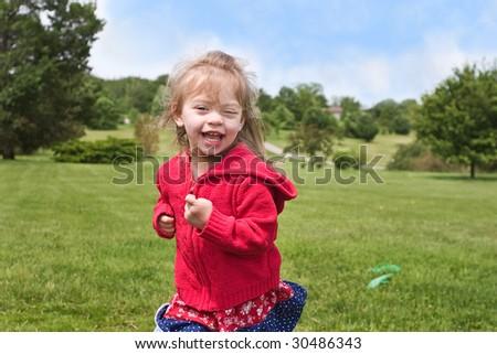 Toddler happily running through park - stock photo