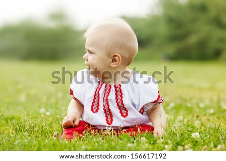 toddler  in russian folk clothes on summer meadow