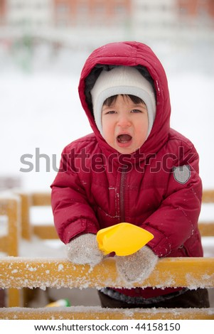 toddler in winter red clothes yells - stock photo