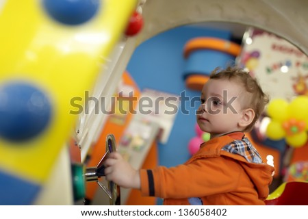 Toddler is playing with amusement machine at indoor playground - stock photo