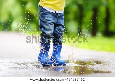 Toddler jumping in pool of water at the summer or autumn day  - stock photo