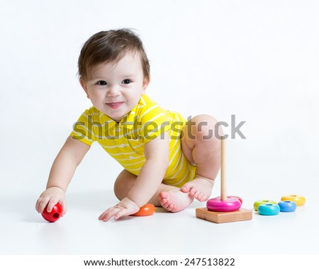 toddler kid playing with colorful toy pyramid