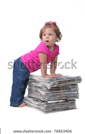 Toddler leaning against stacks of paper ready for recycling, teaching them to care about the environment when they are at an early age. - stock photo