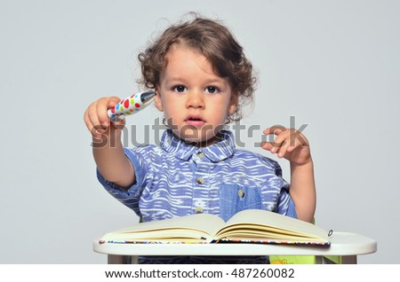 Toddler learning how to write and read. Small kid having fun preparing for school and drawing on a book