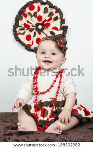 toddler little girl  in traditional spanish red dress. Adorable child from Andalusia with curly hair dancing Gypsy dance. Portrait of artist baby in carnival bellydancing costume  - stock photo