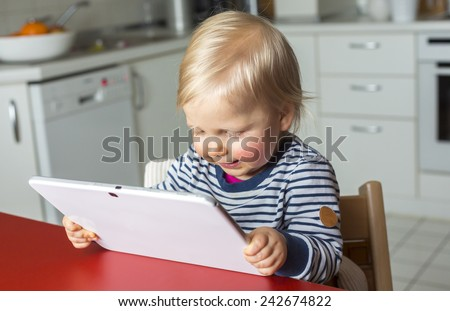 Toddler on a highchair reading a tablet pc - stock photo