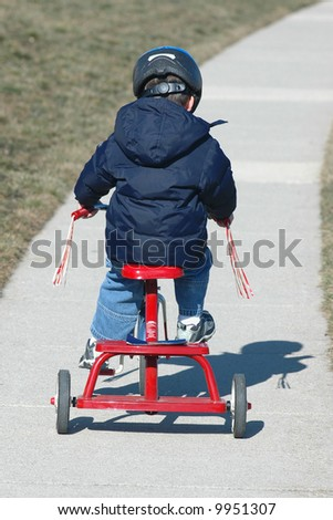 Toddler on Tricycle with Helmet On