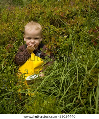 Toddler (one year old) sitting in a forest eating bilberries (european blueberries). - stock photo