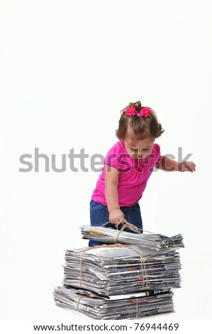 Toddler placing a stack of paper ready for recycling, teaching them to care about the environment when they are at an early age. - stock photo