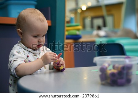 Toddler play in kindergarten - stock photo