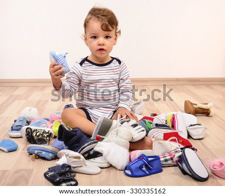 Toddler playing with a lot of baby shoes holding one shoe up. Untidy stack of child shoes thrown on the ground.  - stock photo