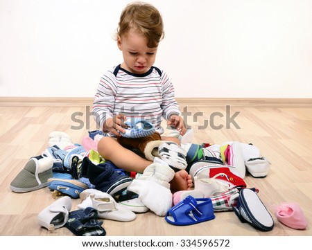 Toddler playing with a lot of baby shoes. Untidy stack of child shoes thrown on the ground. - stock photo