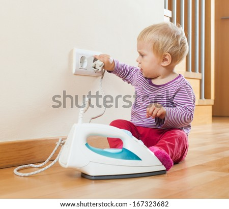 Toddler  playing with electric iron at home - stock photo