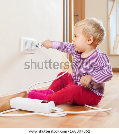 Toddler playing with electrical cord on floor at home