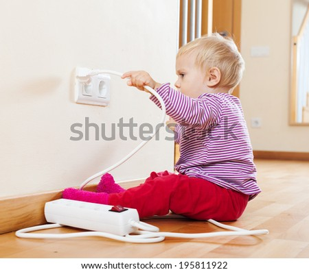 Toddler playing with electricity on floor