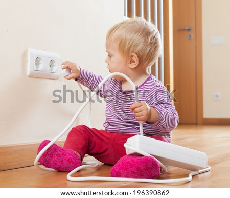 Toddler playing with extension cord at home - stock photo