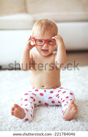Toddler playing with glasses on a white carpet at home - stock photo