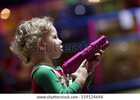 Toddler playing with pistol at indoor playground - stock photo