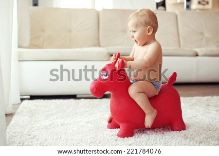 Toddler playing with toy on a white carpet at home - stock photo