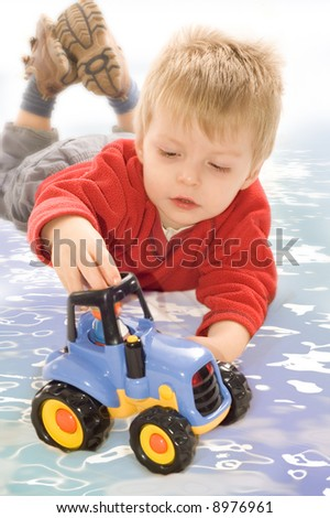 Toddler playing with toy tractor - stock photo
