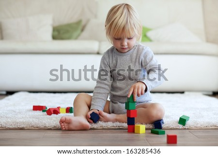 Toddler playing with wooden blocks at home - stock photo