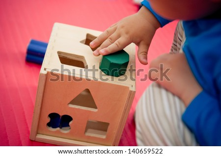 Toddler playing with wooden shape sorter - stock photo