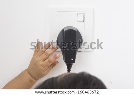 Toddler pulls for an electric wire - stock photo