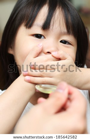 Toddler refusing to take medication - stock photo