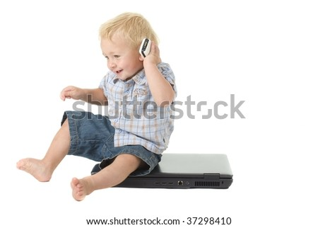 toddler sits on laptop while talking on cellular phone - stock photo