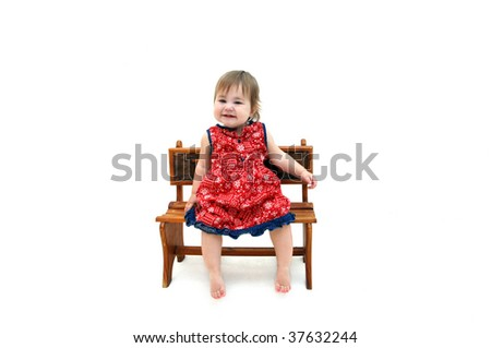 Toddler sits on wooden bench and smiles.  She is wearing a red paisley print dress and is barefoot.  All white room.