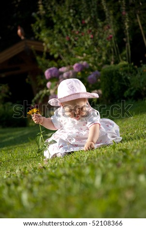 toddler sitting in the meadow and plays - stock photo