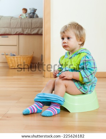 Toddler sitting on green potty in home - stock photo
