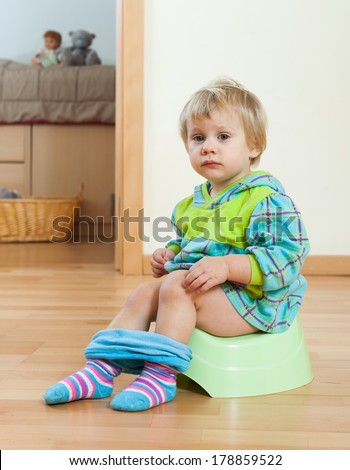 Toddler sitting on green potty in home interior - stock photo
