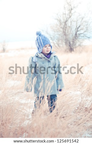 Toddler stands in the snow and tall grass. - stock photo