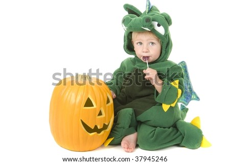 Toddler wearing halloween dragon costume with pumpkin - stock photo