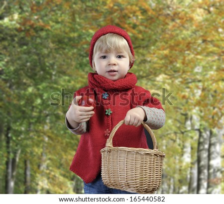toddler with apple and basket, outdoors in autumn