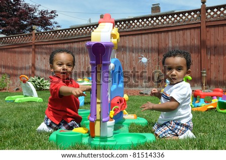 Toddlers Sitting in Suburban Fenced Backyard on Lush Green Grass Looking at Camera Playing with Toys - stock photo