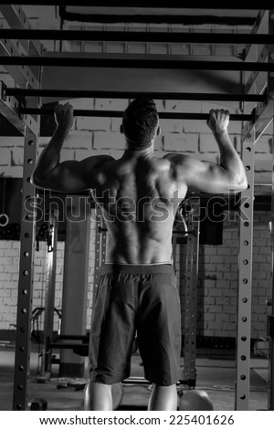 Toes to bar back man pull-ups 2 bars workout - stock photo