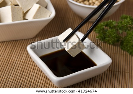 Tofu cheese cubes, soy sauce and beans. - stock photo