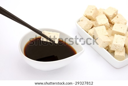 Tofu cubes, soy sauce and chopsticks. Focus on tofu cube on chopstick. - stock photo