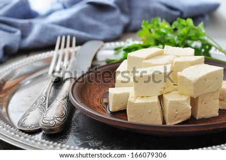 Tofu on plate with fresh tomato on metal tray - stock photo