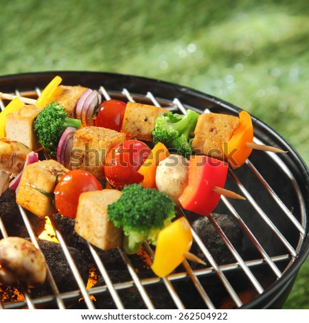 Tofu skewers with colorful vegetables including broccoli, sweet pepper,smoked tofu, tomatoes , onions and mushrooms, grilling on a barbecue - stock photo
