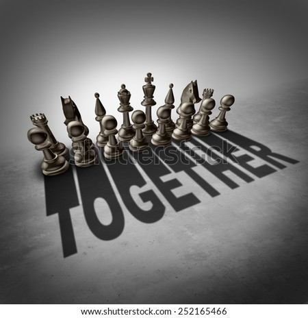 Together concept and team effort symbol as a group of chess pieces in a set casting a shadow with the word representing partnership solidarity in a company or union of workers. - stock photo