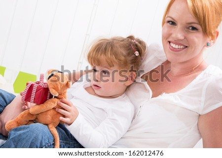 Together: daughter sitting on mother's lap with present isolated on white background