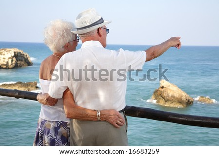 together into the future - senior couple looking into the distance holding each other - stock photo