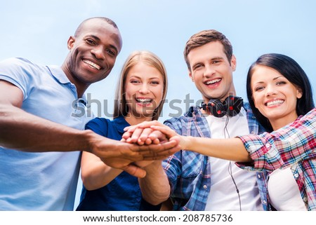 Together we are stronger. Low angle view of four happy young people bonding and holding hands clasped with blue sky in the background - stock photo